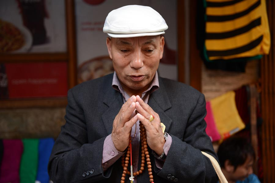 An exile Tibetan prays during a prayer session in Majnu ka Tilla