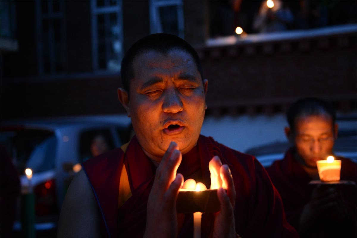 An exile Tibetan monk prays during a candlelight vigil to mourn the death of Lobsang Thokmay.