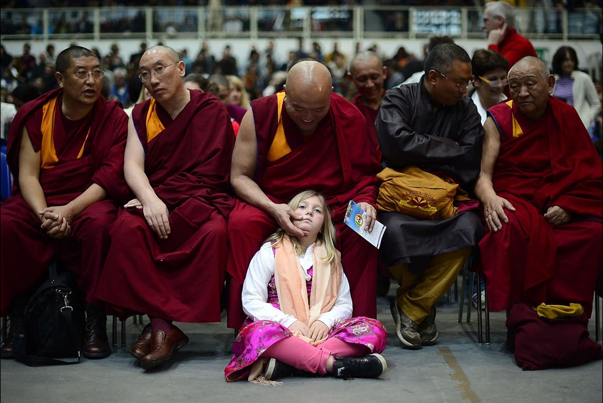 A girl sits by Buddhist monks in Trento
