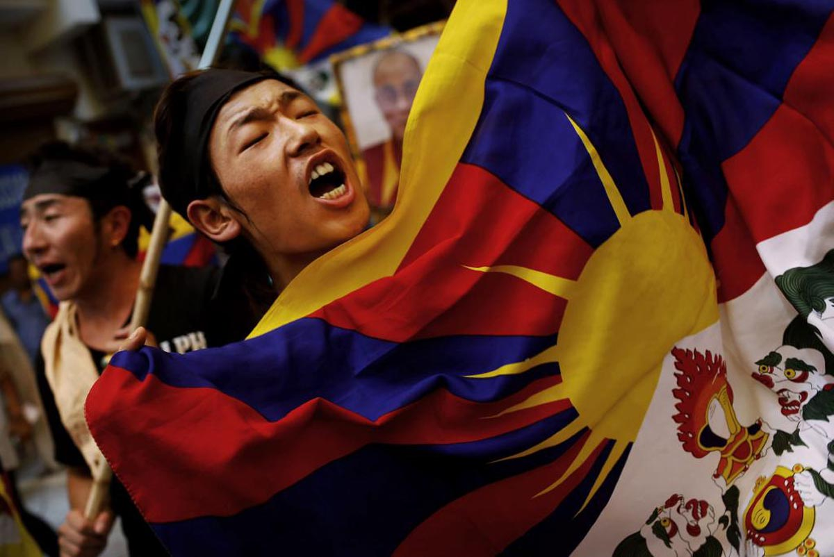 An exiled Tibetan holds a Tibetan flag