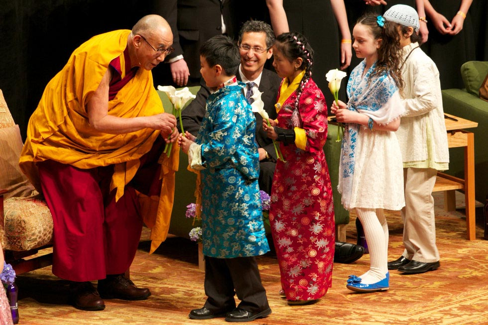Children offer flowers to the Dalai Lama.