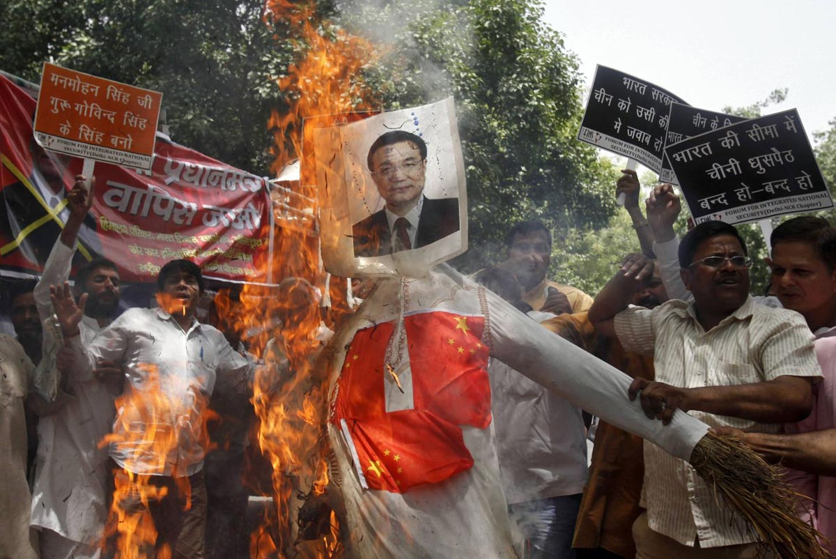 Demonstrators burn an effigy of Chinese Premier Li Keqiang